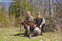 Two hunters with a wild turkey.