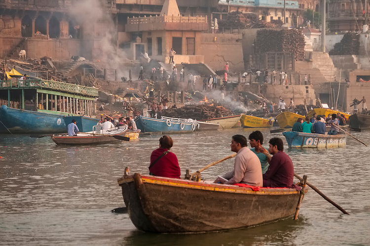 The burning wood piers at the cremation site of Varanasi's Ganges riverfront fill the air with smoke.  The resulting ashes are eventually poured into the Ganges waters.
