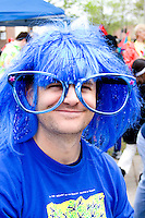 Costumed man age 32 wearing blue wig and giant glasses for the parade. MayDay Parade and Festival. Minneapolis Minnesota USA