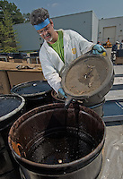 A hazardous waste worker pours used vehicle oil into a storage drum after it was dropped off at a hazardous waste disposal site in Westerville, Ohio. Homeowners were able to remove any hazardous waste from their homes to be properly recycled or disposed of instead of placing in their trash or pouring down the drain.<br />