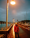 USA, Washington State, boat captain standing on pier in the rain, San Juan Island