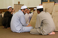 Zliten, Libya. Young Men Review Verses from the Koran Written on their Prayer Boards.  They study to memorize the Koran, working under the supervision of a teacher, or muqri.  The men wear the traditional white hat, or tagiyah.