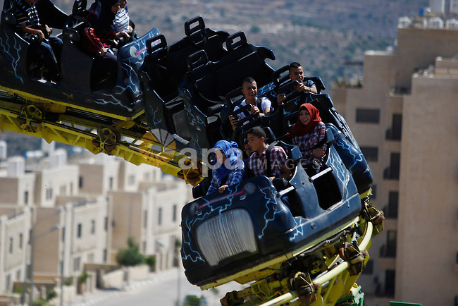 Palestinians enjoy playing games at Sky Land amusement, in the West Bank city of Ramallah, on July 18, 2015, on the second day of Eid al-Fitr holiday which marks the end of the Muslim holy month of Ramadan. Photo by Shadi Hatem