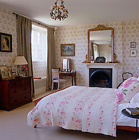 The feminine main  bedroom has been decorated using curtains made from dyed antique linen sheets and Colefax and Fowler's 'Bowood' wallpaper.