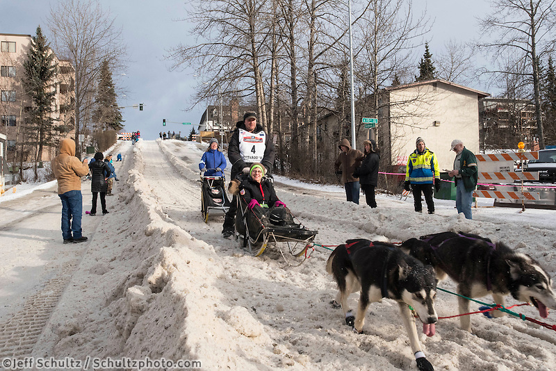 Nathan Schroeder and team run past spectators on the bike/ski trail with an Iditarider in the basket during the Anchorage, Alaska ceremonial start on Saturday, March 5, 2016 Iditarod Race. Photo by O'Hara Shipe/SchultzPhoto.com