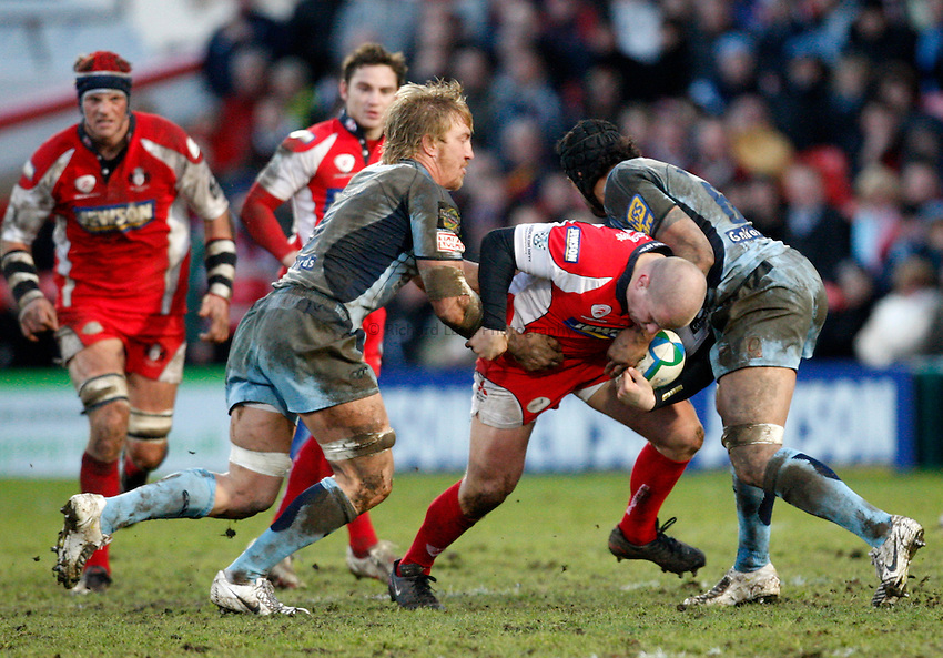 Photo: Richard Lane/Richard Lane Photography. Gloucester Rugby v Cardiff Blues. Heineken Cup. 18/01/2009. Gloucester's Nick Wood is tackled by Cardiff's Andy Powell (lt) and Maama Molitika.