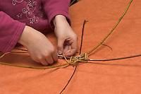 Kinder flechten Nistkugel für Vögel, Vogel, Nisthilfe, Nest, Kugelnest. Mädchen, Kind legt Speichen aus Weidenzweigen und beginnnt dazwischen mit dem Flechten