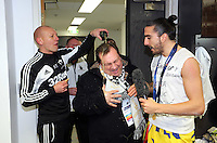 Pictured: Swansea City FC chaplain Kevin Johns (C) has beer poured over his head by goalkeeping coach Adrian Tucker (L) while interviewing Chico Flores (R) in the changing room after the game. Sunday 24 February 2013<br />