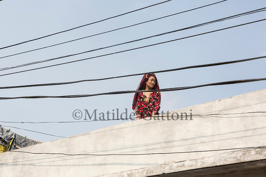 Nepal - Kathamndu - A woman stands on top of her terrace overlooking  the new neighborhood of Kapan mostly inhabitated by workers originally from the Therai region who have moved to the city after coming back from the Gulf. The money earned abroad is usually invested in a house rather than a business and workers prefer to resettle in the capital in order to start a new and anonymous life, far from the issues they often face due to the cast system they are trapped in.