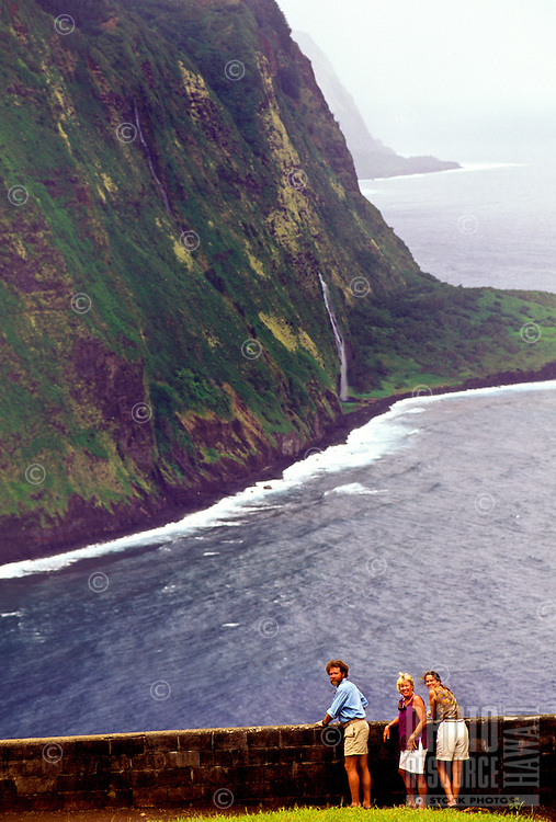 Tourists pause at an overlook to view spectacular Waipio Valley on the lush Hamakua coast, Big Island of Hawaii.