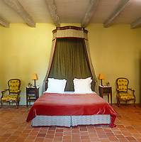 The grand bedroom has a bed with a corona and a red velvet bed cover