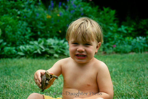 Young boy holds turtle in garden