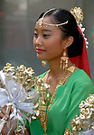 Malaysian Dancer - Malaysian female dancer in traditional costume and gold jewelry holding a bouquet of gilded artificial flowers.