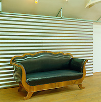 A leather-upholstered Biedermeier sofa stands against a corrugated iron sliding cupboard door in this artist's studio