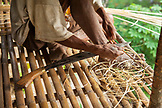 PHILIPPINES, Palawan, Barangay region, a Batak man shaves thin long piceces of bamboo that are used to tie the structural poles of their huts together in Kalakwasan Village