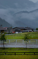 Clouds in the mountains looking over farm buildings. Imst district, Tyrol/Tirol, Austria, Alps.