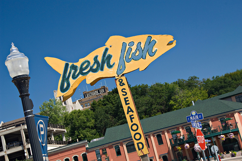 A sign for fresh fish and buildings in downtown Marquette Michigan.