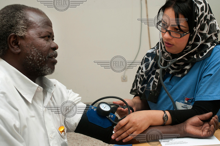 Dr Asma, a Tunisian doctor, takes the blood pressure of a patient at the Nalut Hospital.