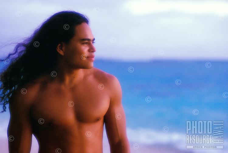 Young Hawaiian man at sunrise on the beach, Oahu