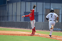 GCL Phillies East first baseman Cesar Rodriguez (12) stretches for a throw as Hemmanuel Rosario (7) runs up the base line during a Gulf Coast League game against the GCL Yankees East on July 31, 2019 at Yankees Minor League Complex in Tampa, Florida.  GCL Yankees East defeated the GCL Phillies East 11-0 in the first game of a doubleheader.  (Mike Janes/Four Seam Images)