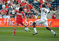 Chicago midfielder Sebastian Grazzini (10) takes a shot with Toronto defender Andy Iro (3) in pursuit.  The Chicago Fire defeated Toronto FC 2-0 at Toyota Park in Bridgeview, IL on August 21, 2011.