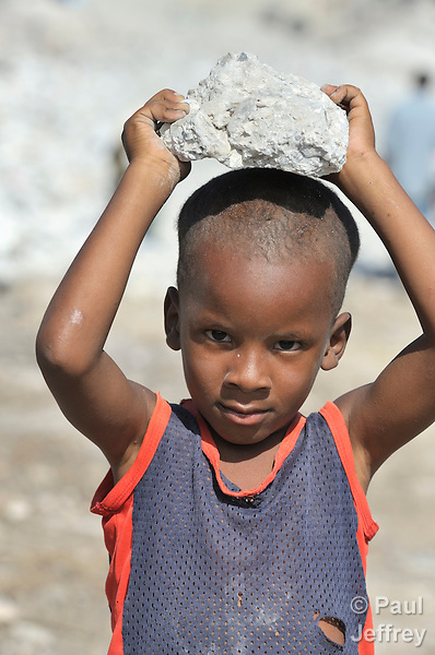 A boy carries pieces of earthquake rubble for his family to construct a temporary shelter in a spontaneous camp for quake survivors being established in Croix-des-Bouguets, Haiti, north of the capital Port-au-Prince. Quake survivors continue to move as aftershocks continue, and reports of aid deliveries in one camp will provoke families from other camps to migrate there.