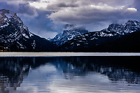 Winter storm clouds begin to clear off 11, 695 foot high Square Top Mountain and Green River Lake in the Wind River Mountains, Wyoming.