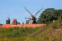 Man running past historical windmill in Copenhagen, Denmark.