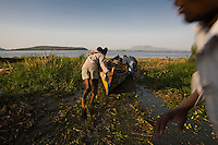 Laucnhing the fishing boat into lake Victoria. Homa Bay Kenya