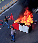 Lebanese protesters hold Lebanese flags as others burn tires and garbage containers to block a main road, during ongoing protests against the Lebanese government, in Beirut, Lebanon, June 6, 2020. Lebanese riot police fired tear gas at protesters in central Beirut, after a planned anti-government demonstration quickly degenerated into rioting and stone-throwing confrontations between opposing camps. Photo by Haitham Al-Mousawi