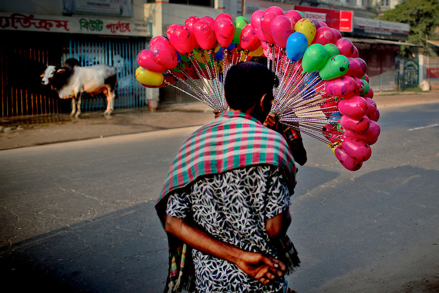 A Bangladeshi street vendor walks with balloons for sale on a street during the day of Eid al-Adha in Mymensingh, outskirts of Dhaka, Bangladesh.
