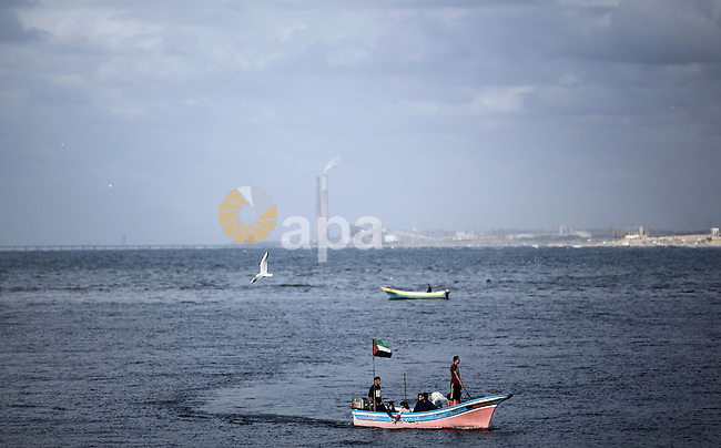 Palestinians ride a boat in the sea in Gaza City during the power cut in Gaza City November 29, 2013. Chief of the Palestinian Power Authority Omar Kittanah said Tuesday that the Palestinian Authority was exerting serious efforts to end the coastal enclave's power crisis which resulted from a lack of fuel to run Gaza's sole power plant. Photo by Ali Jadallah