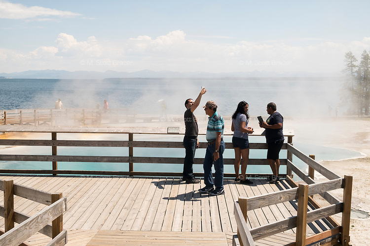 A man takes a selfie on the boardwalk overlooking the Blackpool geyser pool in the West Thumb Geyser Basin area of Yellowstone National Park, Wyoming, USA.