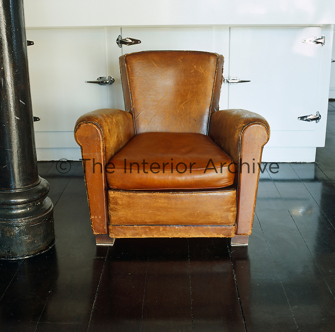 A traditional worn leather armchair stands on the highly polished wooden floor of this industrial New York loft space