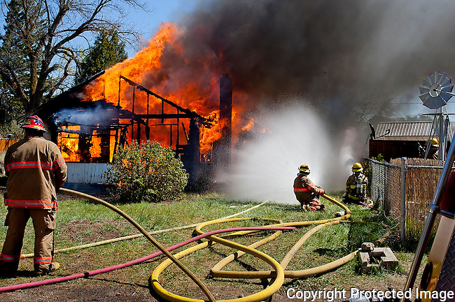 Firefighters put water on a burning home during a training fire in Kittitas, Saturday, April 26, 2014. (Brian Myrick / Daily Record)