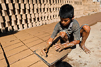 Brian, a ten-year-old Salvadoran boy, works at a brick factory in Istahua, El Salvador, 21 December 2013. Child labour is a common practice at the artisanal brick factories, found mainly in rural areas of El Salvador. Poverty and insufficient earnings in agriculture force parents to employ their own children, in an effort to ensure the livelihood for the whole family. Children aged 8-10 are allowed to work slower, with smaller volumes of clay, while children aged 12 and up work regularly, 8-10 hours a day, 6 days a week.