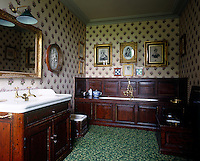 A dark-panelled bath and washbasin strike a note of contrast against the pink floral wallpaper of the bathroom