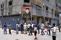 A mural of 14 years old Martyr Hamde Muhsan is seen at the streets of  the Beach Refugee Camp in Gaza, as people work to put ithe portrait in the streets of the Camp. Hamde Muhsan was killed by Israeli army during confrontations in Zeitun, Gaza Strip. As a request of Muhsan family, Faiez el Hazani painted him wearing military clothes. Photo by Quique Kierszenbaum