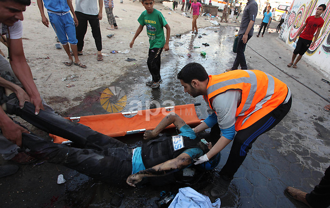 Palestinian men move the body of Palestinian journalist, Rami Rayan, the victim of an Israeli air strike on a market place to an ambulance in the Shejaiya neighbourhood near Gaza City on July 30, 2014. At least 15 people were killed and 150 people wounded in an Israeli air strike on a market near Gaza City, medics said. The strike came shortly after the Israeli army said it was observing a humanitarian lull that would be in force for four hours from 1200 GMT. Photo by Ashraf Amra