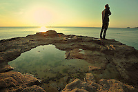 Person fishing from a rock with rock pool at sunset at Perranporth, Cornwall.