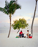 USA, Florida, friends in conversation grilling fish at beach, Islamorada