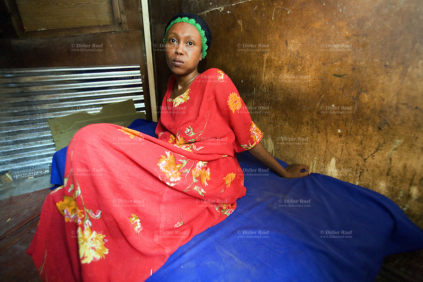 "Djibouti. Djibouti province. Djibouti town. Quartier 2. Fatouma is a black muslim commercial sex worker (CSW). She seats on the bed in her tiny room where she prostitutes herself for 300 Djibouti Francs ( around 1.5 US$). She always use condoms with her customers. Sabah is one of the prostitutes belonging to the association Al-Salaam, which means ""Soeur à Soeur"" (Sister to sister). The Global Fund through the djiboutian Ministry of Health supports the condoms distribution with an Aids grant (financial aid). Fatouma is chewing khat which is a flowering plant native to tropical East Africa and contains the alkaloid cathinone, an amphetamine-like stimulant which causes excitement and euphoria. Djiboutian men and women usualy chew in the afternoon hours. Khat is considered as a drug which abuse can produce mild to moderate psychic dependence.  © 2006 Didier Ruef"