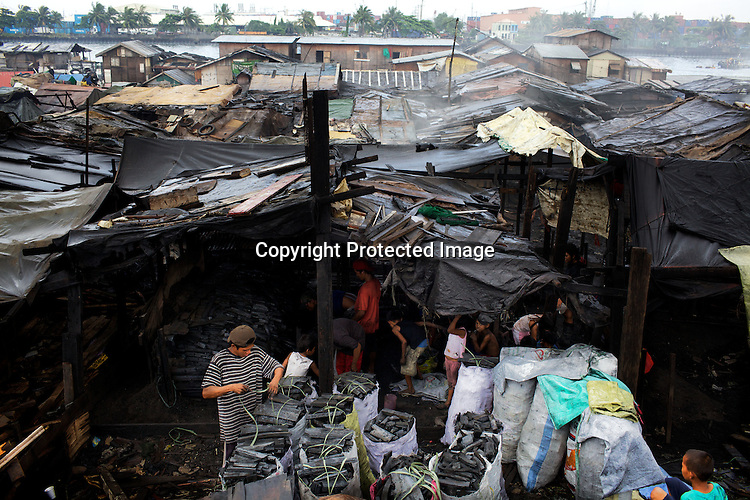 A family works together to pack charcoal into the sacks in the slums of Smokey Mountain-II in Manila in Philippines. Photo: Sanjit Das