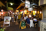 Customers enjoy food and drink at a store along Harmonica Yokocho in the trendy neighborhood of Kichijoji in Musashino City, Tokyo, Japan on 16 Sept. 2012.  Photographer: Robert Gilhooly