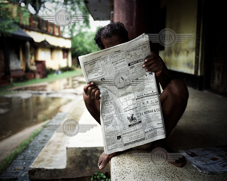 """A man reads the newspaper outside his home in Dhinkia village. All the residents of this village would be displaced if plans for the new steel works are allowed to proceed. South Korean steel giant Posco continues to face stiff public resistance in Orissa's Jagatsinghpur district where the company is setting up India's biggest direct foreign investment project of a 12 million tonne steel plant, at the cost of USD 12 Billion. Villagers have formed an agitating group, """"Posco Pratirdh Sangram Samiti"""" to oppose the construction of the Posco development, which will displace thousands of people and make agricultural land untenable."""