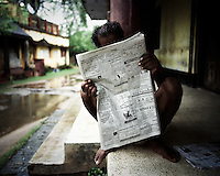 "A man reads the newspaper outside his home in Dhinkia village. All the residents of this village would be displaced if plans for the new steel works are allowed to proceed. South Korean steel giant Posco continues to face stiff public resistance in Orissa's Jagatsinghpur district where the company is setting up India's biggest direct foreign investment project of a 12 million tonne steel plant, at the cost of USD 12 Billion. Villagers have formed an agitating group, ""Posco Pratirdh Sangram Samiti"" to oppose the construction of the Posco development, which will displace thousands of people and make agricultural land untenable."