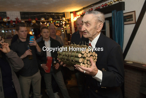 Bill Richards (91 yrs) leads a group of Wassailers, making a short speech before placing the Ashen Faggot onto the fire. The sticks are ash and the 'bonds' are made of willow withies  tied in a 'willow rose'.<br /> <br /> Ashen Faggot or Ashten Fagot is similar to a Christmas party Yule Log, from which the chocolate ones derive. Its placed on a fire on old News Years eve, traditionally by the oldest person in the room. In the past at c as each 'bond' bursts a toast would be drunk. Until recently the brewery provided a barrel of cider and beer, but alas no longer.