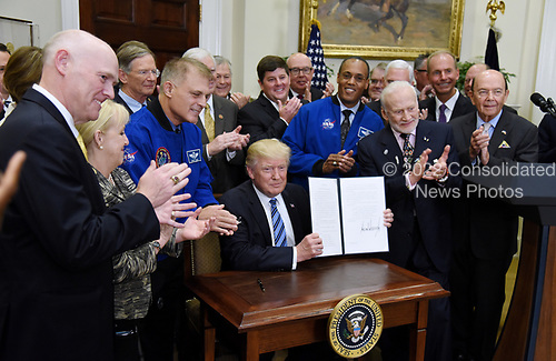 United States President Donald J. Trump, signs an Executive Order to reestablish the National Space Council as Apollo 11 astronaut Buzz Aldrin (R) looks on  in the Roosevelt Room of the White House in Washington, DC, on June 30, 2017.<br /> Credit: Olivier Douliery / Pool via CNP