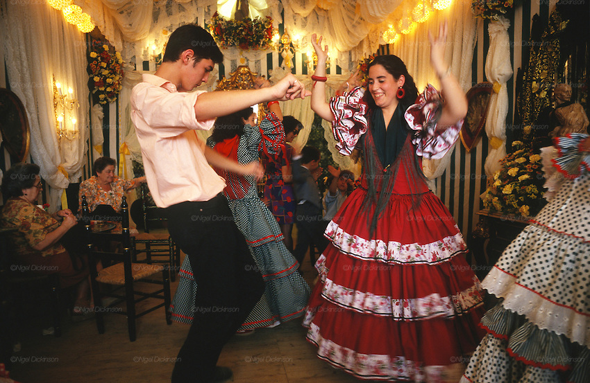 "Everyone wearing traditional dress, men ""traje corto"" and women frilly flamenco dresses. Daytime festivities, eating, dancing, meeting friends and business contacts in the ""casetas"" temporary marquee tents, set up during the Feria..The Feria de abril de Sevilla, ""Seville April Fair"" dates back to 1847. During the 1920s, the feria reached its peak and became the spectacle that it is today. It is held in the Andalusian capital of Seville in Spain. The fair generally begins two weeks after the Semana Santa, Easter Holy Week. The fair officially begins at midnight on Monday, and runs six days, ending on the following Sunday. Each day the fiesta begins with the parade of carriages and riders, at midday, carrying Seville's citizens to the bullring, La Real Maestranza...For the duration of the fair, the fairgrounds and a vast area on the far bank of the Guadalquivir River are covered in rows of casetas (individual decorated marquee tents which are temporarily built on the fairground). Some of these casetas belong to the prominent families of Seville, some to groups of friends, clubs, trade associations or political parties. From around nine at night until six or seven the following morning, at first in the streets and later only within each caseta, crowds of people party and dance Sevillanas, traditional Flamenco dances, Sevillan style drinking Jerez sherry, or Manzanilla wine, and eating tapas. Men and women dress up in their finery, the traditional ""traje corto"" (short jacket, tight trousers and boots) for men and the ""faralaes"" or ""trajes de flamenca"" (flamenco style dress) for women. The men traditionally wear hats called ""cordobés""."