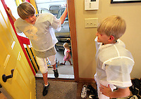 Brayden Jacobs, 11, talks with his brother, Justin, 10, as little sister Ella, 3, waits with them to depart for a night of activities.  The trio, and their two other brothers, lost their father, Eric, in a plane crash in 2006.  They have since been raised by their mother, Heather, in Polk City.